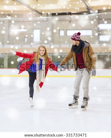 people, friendship, sport and leisure concept - happy couple holding hands on skating rink - stock photo