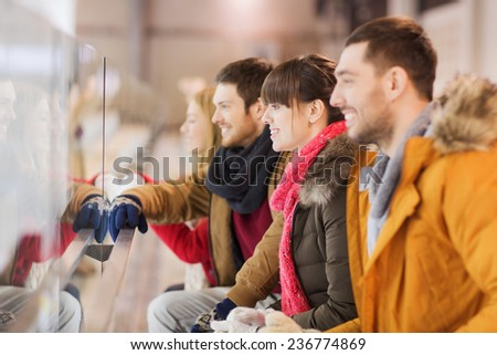 people, friendship, sport and leisure concept - happy friends watching hockey game or figure skating performance on skating rink - stock photo