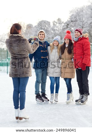 people, friendship, technology and leisure concept - happy friends taking picture with smartphone on ice skating rink outdoors - stock photo
