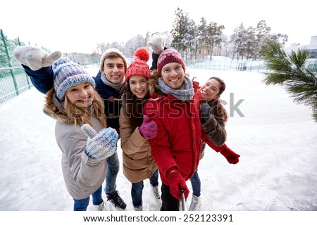 people, friendship, technology and leisure concept - happy friends taking picture with smartphone selfie stick and showing thumbs up on ice skating rink outdoors - stock photo