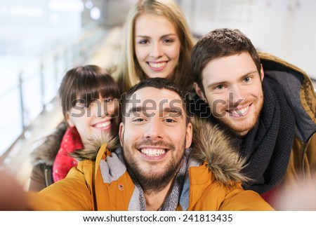 people, friendship, technology and leisure concept - happy friends taking selfie with camera or smartphone on skating rink - stock photo