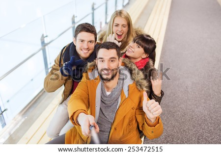 people, friendship, technology and leisure concept - happy friends taking selfie with camera or smartphone and selfie stick on skating rink - stock photo