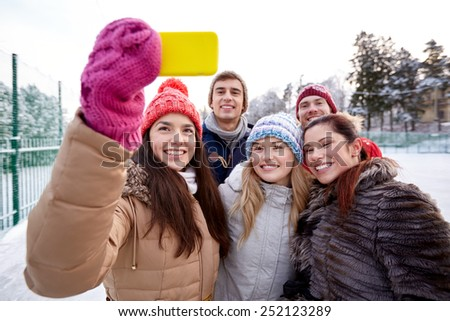 people, friendship, technology, winter and leisure concept - happy friends taking selfie with smartphone outdoors - stock photo