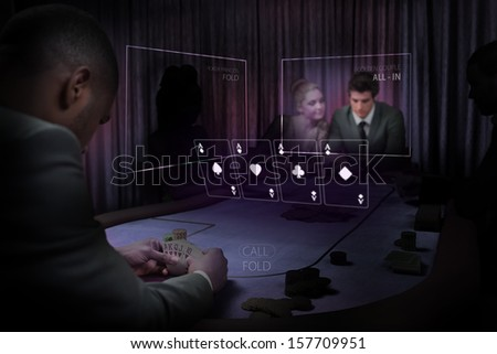 People gambling on table in purple light with holographic card display in dark room - stock photo