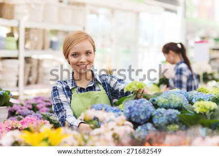 people, gardening and profession concept - happy woman or gardener taking care of flowers in greenhouse - stock photo