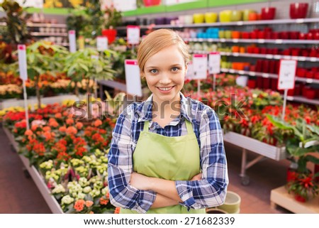 people, gardening and profession concept - happy woman with flowers in greenhouse - stock photo