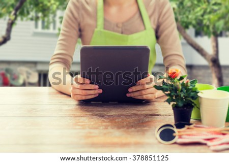 people, gardening, flowers and profession concept - close up of woman or gardener holding tablet pc computer and sitting at wooden table over summer house background - stock photo