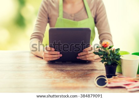 people, gardening, flowers and profession concept - close up of woman or gardener holding tablet pc computer and sitting at wooden table over green natural background - stock photo