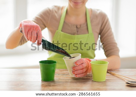 people, gardening, seeding and profession concept - close up of woman hands with trowel burying seeds in soil - stock photo
