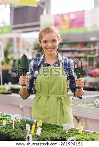 people, gardening tools and profession concept - happy woman or gardener with trowel and fork in greenhouse