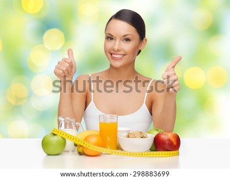 people, gesture and diet concept- happy asian woman with healthy food showing thumbs up over green lights background - stock photo