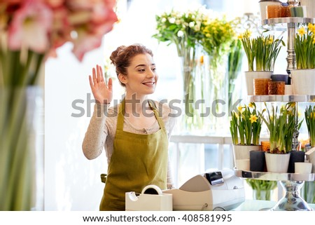 people, gesture, business, sale and floristry concept - happy smiling florist woman waving hand at flower shop cashbox - stock photo