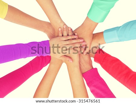 people, gesture, gay pride and homosexual concept - close up of women hands in rainbow clothes on top of each other over white background - stock photo
