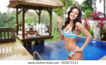people, gesture, summer holidays, travel and tourism concept- happy woman in bikini swimsuit showing victory hand sign over hotel resort background - stock photo