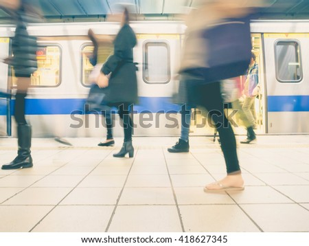 People getting off the subway train. Motion blur. City life. Toned image. - stock photo