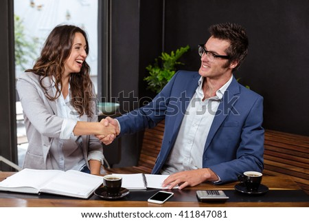 People giving handshake in a cafe - stock photo