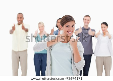 people giving the thumbs-up with a woman smiling in foreground against white background - stock photo