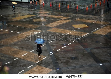 People go across the square in a rainy day. - stock photo