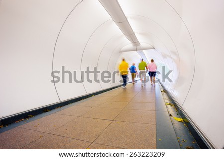People go through the underpass. Abstract photo from the center of Singapore - stock photo