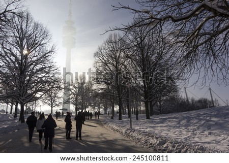 People going for a walk in Munich's Olympiapark on a sunny and snowy winter day. - stock photo