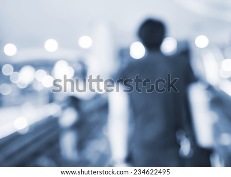 People going up the escalator with bokeh. Blur background. - stock photo