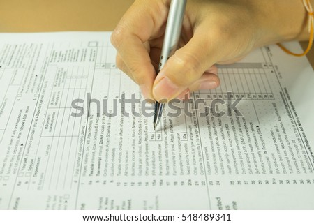 People hand filling income tax form