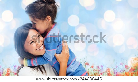people, happiness, love, family and motherhood concept - happy mother and daughter hugging over blue lights and poppy field background - stock photo