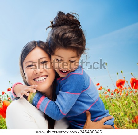 people, happiness, love, family and motherhood concept - happy mother and daughter hugging over blue sky and poppy field background - stock photo