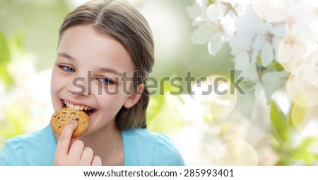 people, happy childhood, food, sweets and bakery concept - smiling little girl eating cookie or biscuit over green natural background - stock photo