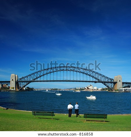 People have a rest in the middle of the day in from of the Sydney Harbour Bridge - stock photo