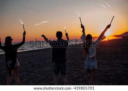 People have fun at night on a beach. Silhouette of friends with firecracker. 4th of July - stock photo