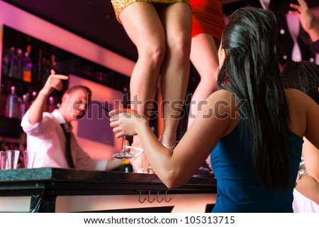 People having a party in club or bar, two women are dancing on the table - stock photo