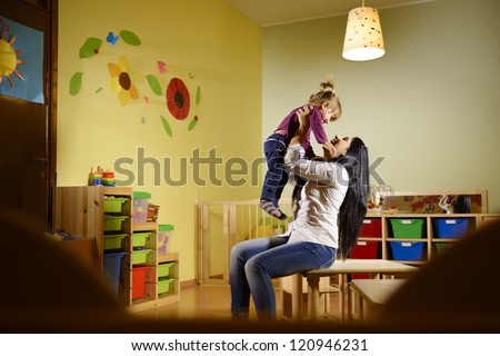 People having fun at school, female educator lifting mid-air child in kindergarten - stock photo
