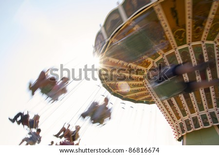 People having fun on a retro chairoplane at a fair - stock photo