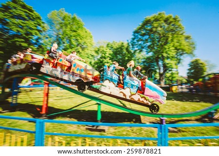 People Having Fun On Rollercoaster In The Park. Photo With Zoom Blur For Motion Effect - stock photo