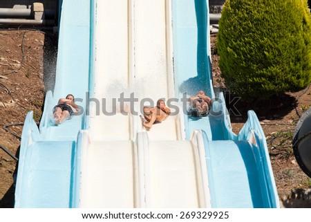 People having fun, sliding at water park. - stock photo