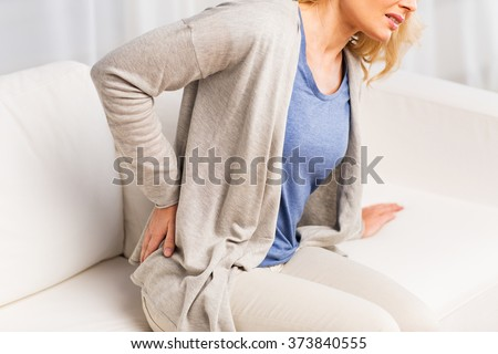 people, healthcare and problem concept - close up of unhappy woman suffering from pain in back or reins at home - stock photo