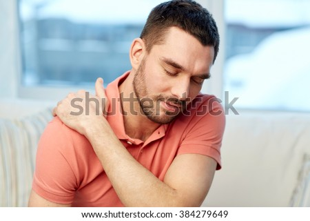 people, healthcare and problem concept - unhappy man suffering from neck or shoulder pain at home - stock photo