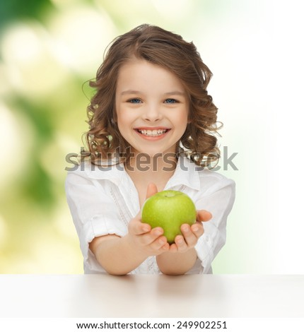 people, healthy food, children and happiness concept - happy girl with green apple over green background - stock photo
