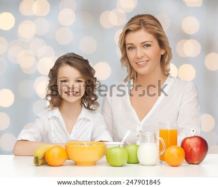 people, healthy lifestyle, family and food concept - happy mother and daughter eating healthy breakfast over holidays lights background - stock photo