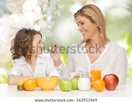 people, healthy lifestyle, family and food concept - happy mother and daughter eating healthy breakfast over green summer garden background - stock photo