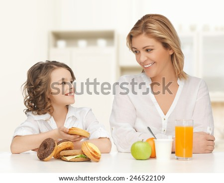 people, healthy lifestyle, family and unhealthy food concept - happy mother and daughter eating different food over home kitchen background - stock photo