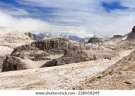 People hiking in Sass Pordoi, Dolomiten, Italia, Europe - stock photo