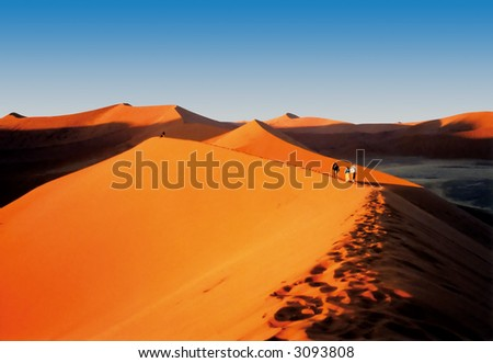 people hiking on beautiful orange namibian sand dunes - stock photo