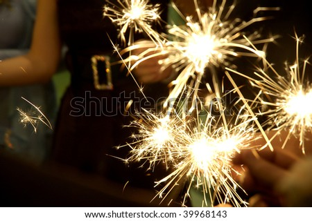 People holding beautiful sparklers (fire crackers) in hands on a birthday, Christmas or New Year party. Useful file for the upcoming holidays and parties. - stock photo