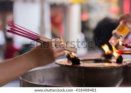 People holding burning incense sticks in chinese temple