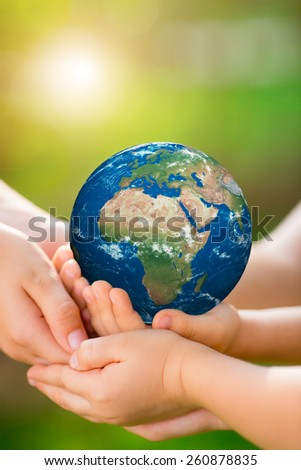 People holding 3d planet in hands against green spring background. Earth day holiday concept. Elements of this image furnished by NASA