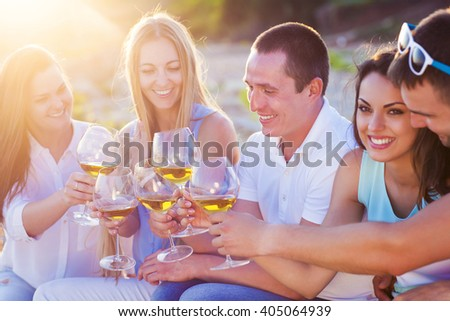 People holding glasses of white wine making a toast at the beach picnic