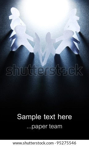 people holding hands on black with white light on top,empty space - stock photo