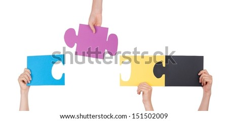 People Holding Pieces of a Puzzle Which Are Fitting, Isolated - stock photo